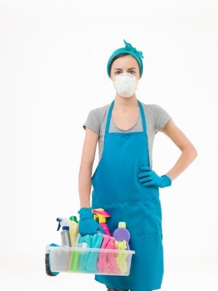 A lady cleaner is wearing a face mask and holding a box of cleaning materials in her right hand.