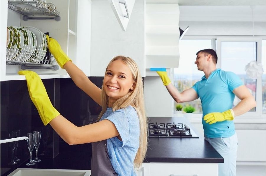 Two cleaners in a kitchen. A pretty blonde lady is stacking dishes and smiling. A man is cleaning in the background.