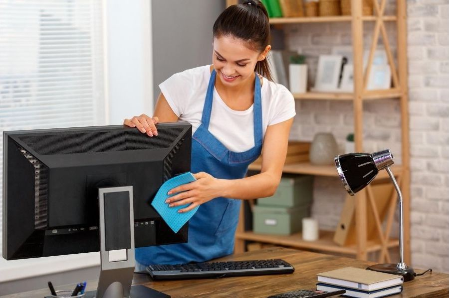 A lady cleaner is wiping a computer monitor with a blue cloth and smiling.