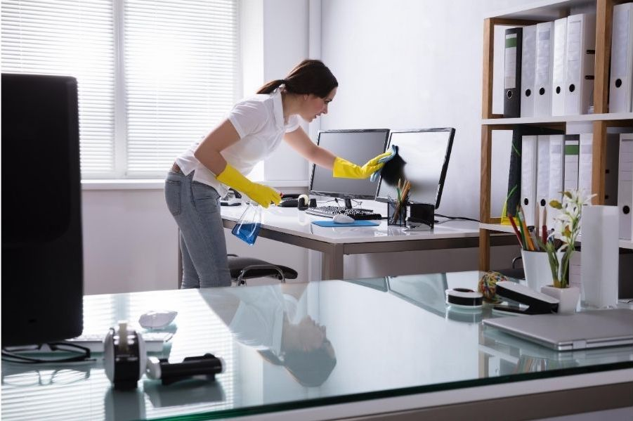 A lady cleaner is wiping the monitor of a computer in an office. In her left hand, she is holding a bottle of cleaning fluid.